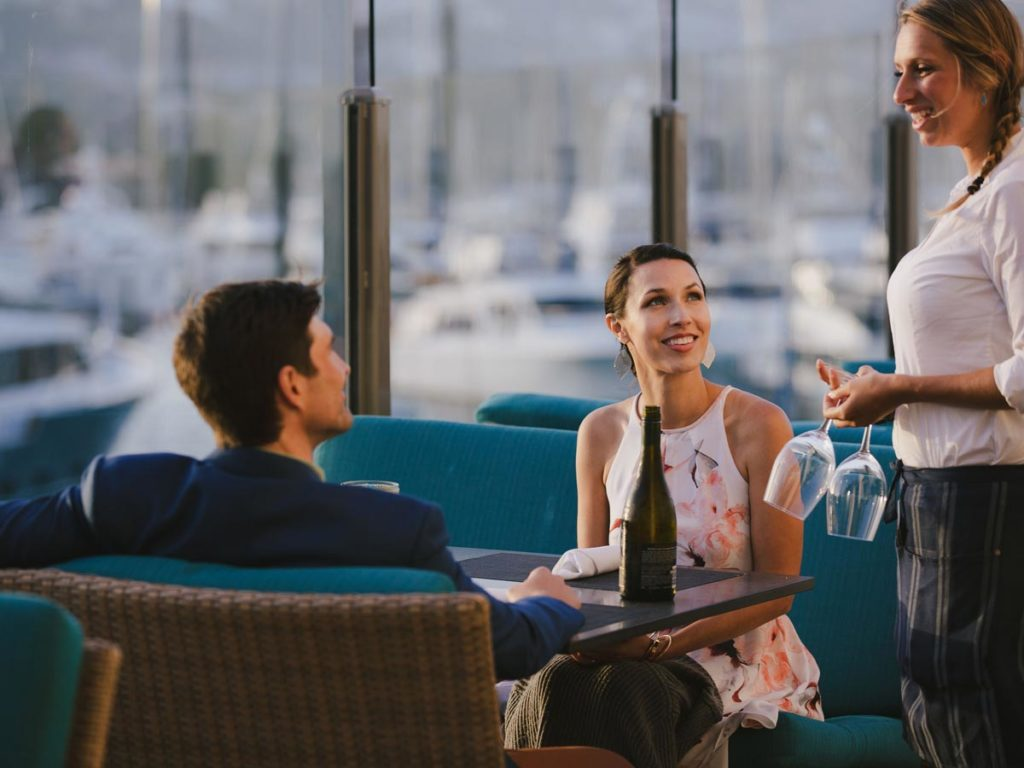 Couple eating at San Diego restaurant with waterfront terrace